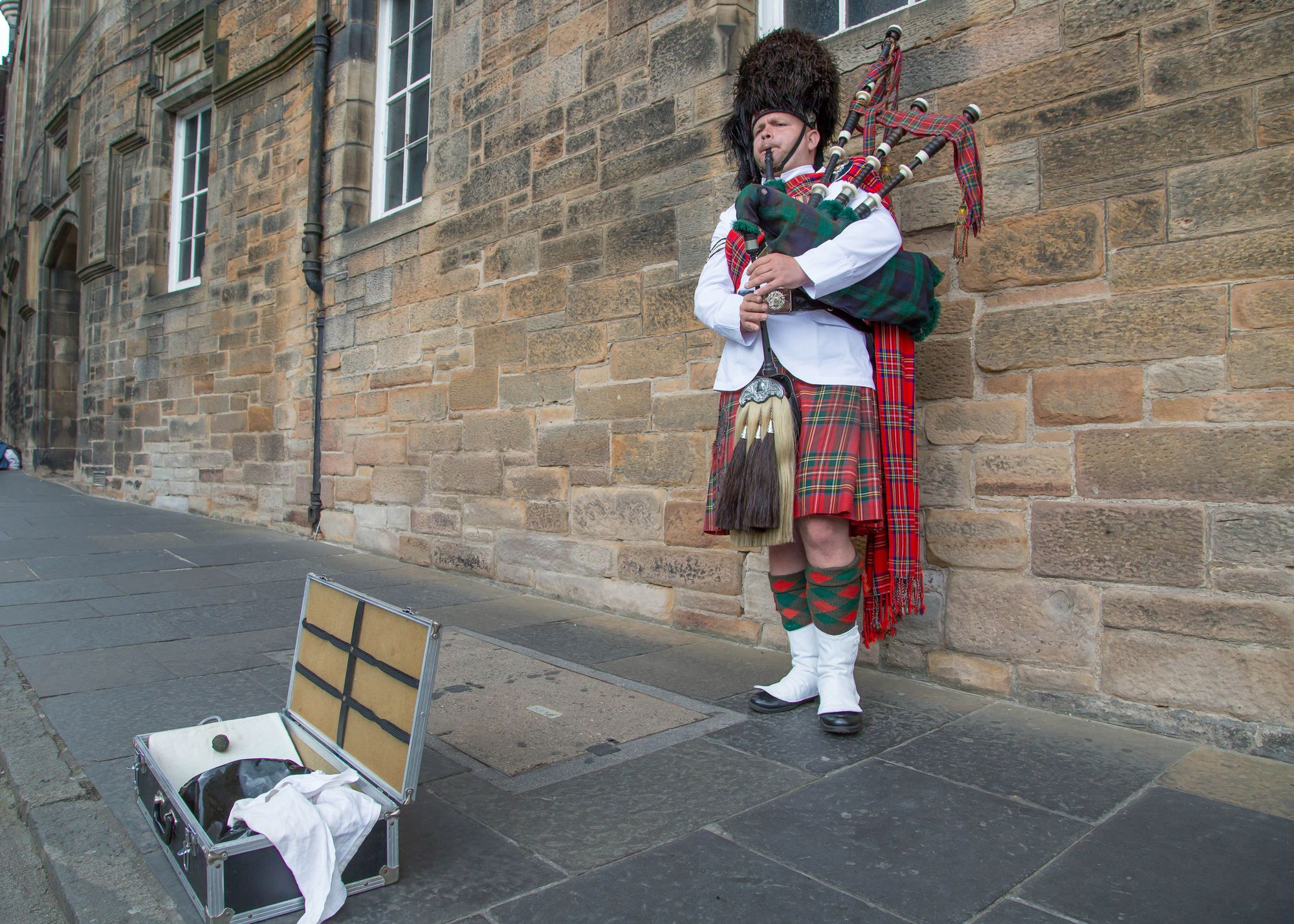 A man plays the bagpipes on the Royal Mile in Edinburgh